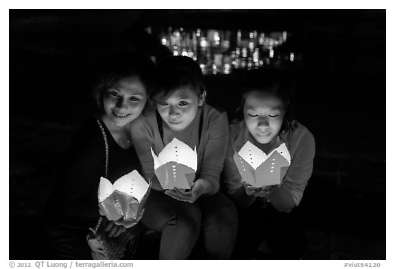 Faces of three women in the glow of candle boxes. Hoi An, Vietnam (black and white)