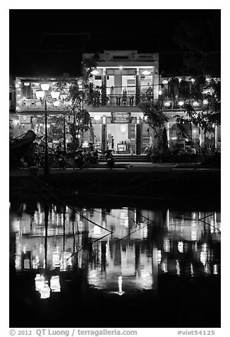 Waterfront house reflected in river at night. Hoi An, Vietnam (black and white)