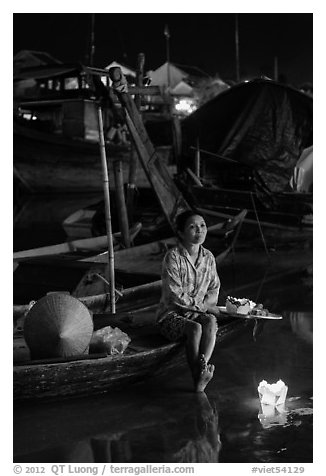 Woman sitting in boat with floating candles by night. Hoi An, Vietnam (black and white)