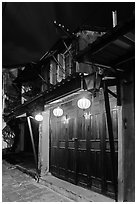 Townhouse with wooden doors lighted by paper lanterns. Hoi An, Vietnam (black and white)