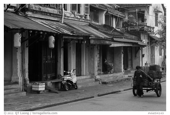 Man pulling cart in front of old townhouses. Hoi An, Vietnam (black and white)