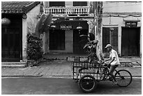 Man riding tricycle cart in front of old townhouses. Hoi An, Vietnam ( black and white)