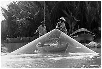 Fisherman pulls up net from rowboat. Hoi An, Vietnam ( black and white)