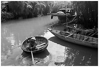 Man rows coracle boat in river channel. Hoi An, Vietnam ( black and white)