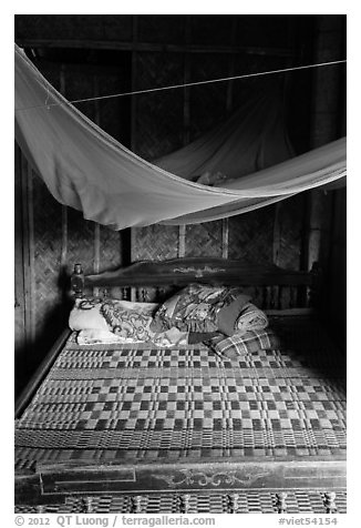 Wooden bed with straw mat and mosquito net, Cam Kim Village. Hoi An, Vietnam (black and white)