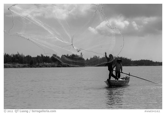 Fisherman throwing net, Thu Bon River. Hoi An, Vietnam (black and white)