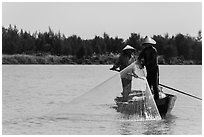 Fishermen standing in boat retrieving net, Thu Bon River. Hoi An, Vietnam (black and white)