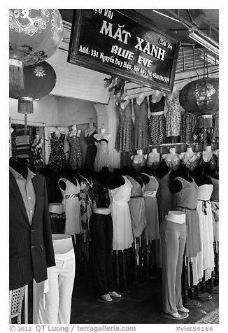 Colorful outfits and lanterns in textile shop. Hoi An, Vietnam (black and white)