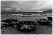Coracle boats on beach during storm. Da Nang, Vietnam (black and white)