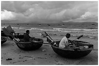 Fishermen mending nets in coracle boats. Da Nang, Vietnam (black and white)