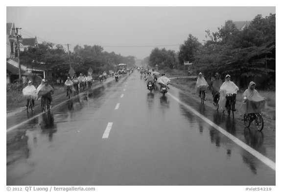 Riders wearing colorful ponchos on wet road on Hwy 1 south of Hue. Vietnam (black and white)