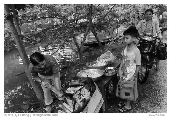 Boy waiting for donut coooked near canal, Thanh Toan. Hue, Vietnam (black and white)