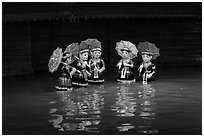 Water puppets (5 characters with umbrellas), Thang Long Theatre. Hanoi, Vietnam (black and white)