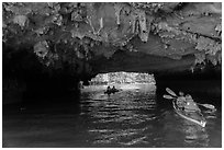 Paddling through Luon Cave tunnel. Halong Bay, Vietnam ( black and white)