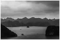 Boat amongst islands under dark sky. Halong Bay, Vietnam (black and white)