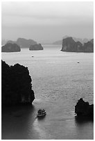 Tour boat navigating between islets. Halong Bay, Vietnam (black and white)