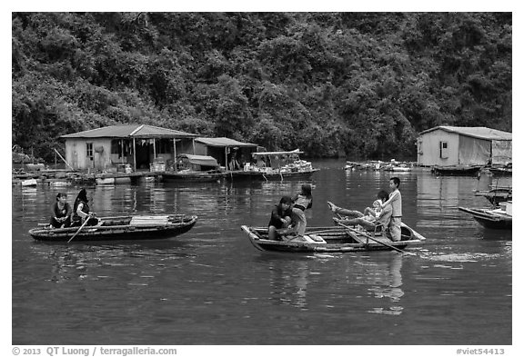 Villagers move between floating houses by rowboat. Halong Bay, Vietnam (black and white)