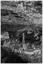 Visitors walking in cavernous chamber, Sungsot cave. Halong Bay, Vietnam (black and white)