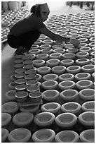 Woman laying ceramic bowls to dry in workshop. Bat Trang, Vietnam (black and white)