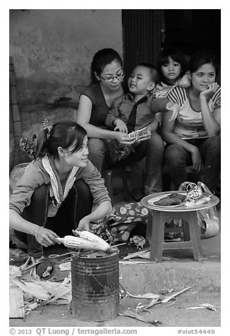 Woman roasting corn in the street. Bat Trang, Vietnam (black and white)