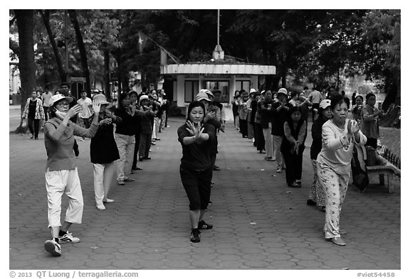 Women practising Tai Chi on shores of Hoang Kiem Lake. Hanoi, Vietnam (black and white)