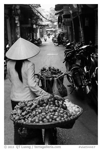 Woman pushing bicycle loaded with vegetable for sale in narrow street, old quarter. Hanoi, Vietnam (black and white)