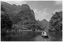 Boat journeying below tall lush cliffs, Trang An. Ninh Binh,  Vietnam (black and white)