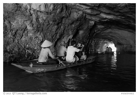 Boat rowed inside grotto passage, Trang An. Ninh Binh,  Vietnam (black and white)