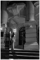 Woman in evening gown entering opera house. Hanoi, Vietnam (black and white)
