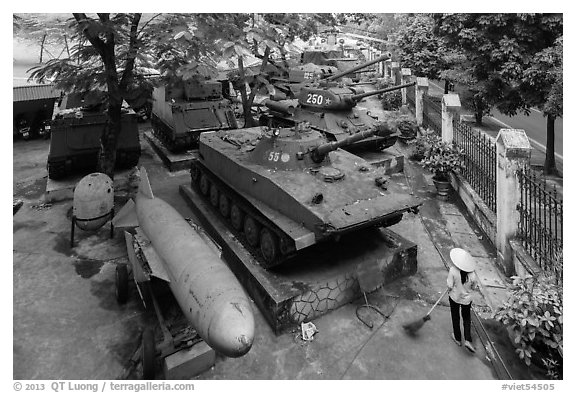 Woman sweeping floor in front of tanks, military museum. Hanoi, Vietnam (black and white)