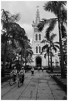 Students biking past Cho Quan Church, district 11. Ho Chi Minh City, Vietnam (black and white)