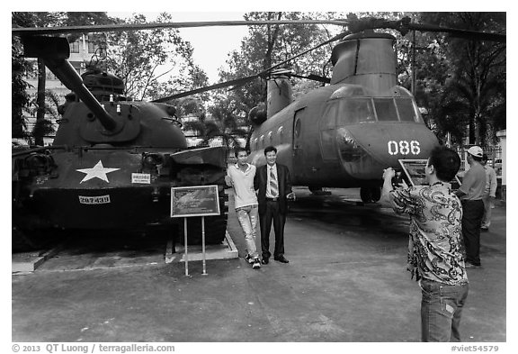 Tourists pose with tanks and helicopters, War Remnants Museum, district 3. Ho Chi Minh City, Vietnam (black and white)