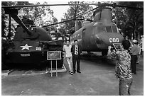 Tourists pose with tanks and helicopters, War Remnants Museum, district 3. Ho Chi Minh City, Vietnam ( black and white)