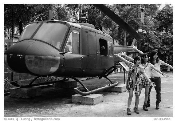 Young women posing with helicopter, War Remnants Museum, district 3. Ho Chi Minh City, Vietnam (black and white)