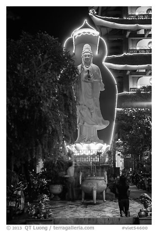 Praying outside Quoc Tu Pagoda at night, district 10. Ho Chi Minh City, Vietnam (black and white)