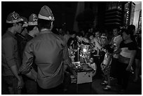 People gather around street hawker on Christmas eve. Ho Chi Minh City, Vietnam (black and white)
