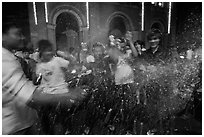 Revellers celebrating with spray in front of Notre Dame Cathedral on Christmas Eve. Ho Chi Minh City, Vietnam ( black and white)