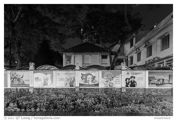 Fenced buildings with propaganda posters at night. Ho Chi Minh City, Vietnam (black and white)