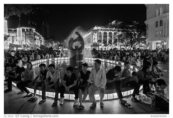 People sitting on fountain at night, New Year eve. Ho Chi Minh City, Vietnam (black and white)