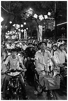 Street packed with motorbikes and bicycle riders at night. Ho Chi Minh City, Vietnam (black and white)