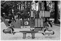 Girls with matching outfits on playground, Van Hoa Park. Ho Chi Minh City, Vietnam (black and white)