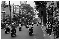Motorbike traffic and pedestrians waiting for bus. Ho Chi Minh City, Vietnam (black and white)