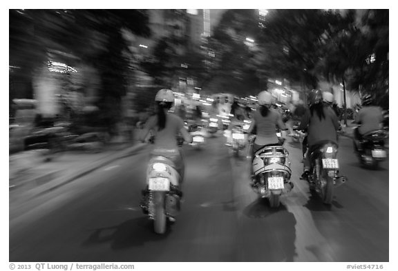 Blurry view from middle of street traffic at night. Ho Chi Minh City, Vietnam (black and white)