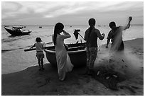 Fishermen folding net out of coracle boat as children watch. Mui Ne, Vietnam ( black and white)