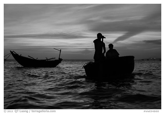 Men silhouetted paddling coracle boat at sunset. Mui Ne, Vietnam (black and white)