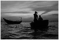Men silhouetted paddling coracle boat at sunset. Mui Ne, Vietnam ( black and white)