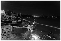 Man with fire next to coracle boat at night. Mui Ne, Vietnam ( black and white)