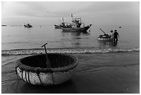 Coracle and fishing boats at dawn. Mui Ne, Vietnam ( black and white)