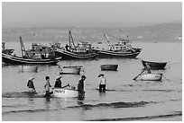 Fishermen use coracle boats to bring back catch from fishing boats. Mui Ne, Vietnam ( black and white)