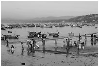 Hawkers gather on mirror-like beach in early morning. Mui Ne, Vietnam ( black and white)